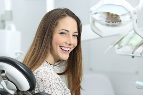 Smiling Patient On Dentist Chair